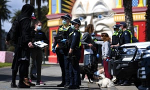Police speak to people ahead of a planned rally in St Kilda
