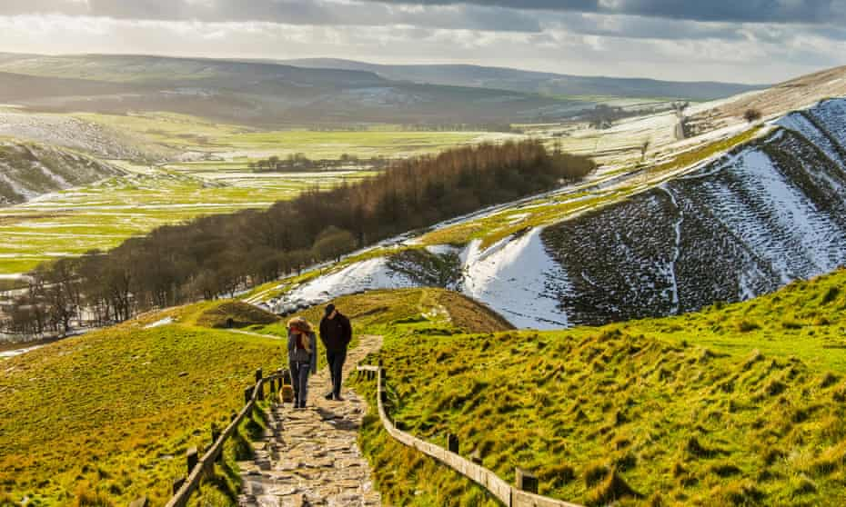 Walkers climb stone steps to the summit of Mam Tor, Derbyshire, UK
