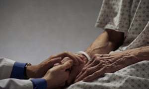 A healthcare worker holds the hands of an elderly patient