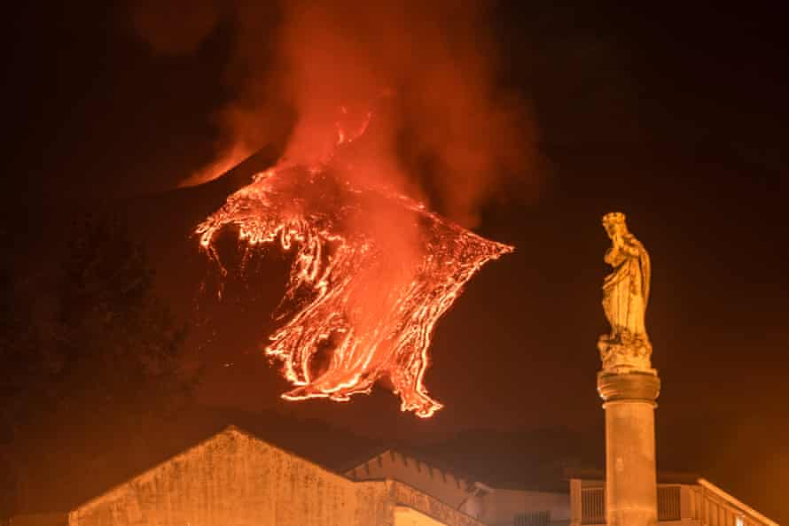 The statue of Virgin Mary near the main church of Milo with the lava flow of an eruption