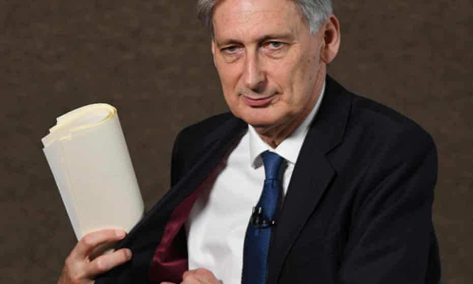 Chancellor Philip Hammond prepares to deliver a speech to trainee bankers in London yesterday. The public spending squeeze is set to tighten soon, with a range of cuts again targeting family benefits.
