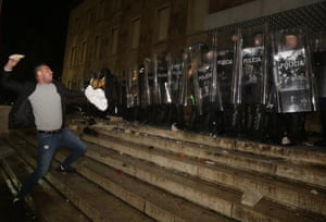 A protester throws a stone at police officers outside the prime's minister office during clashes in Tirana. Hundreds are demanding the interior minister's resignation over the fatal police shooting of a 25-year-old man who had breached a coronavirus-linked curfew.