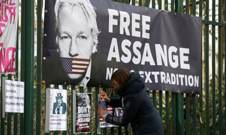 A Julian Assange supporter attaches a sign to a fence outside Woolwich crown court in London.
