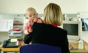 Woman at desk holding baby.