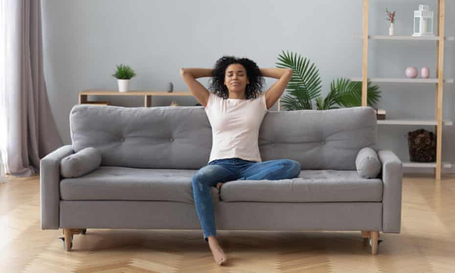 Calm black woman relaxing on comfortable sofa in living roomYoung calm black woman relaxing sit on comfortable sofa in modern living room, lazy happy african woman girl resting on couch breathing fresh air enjoy peace of mind no stress free on couch at home