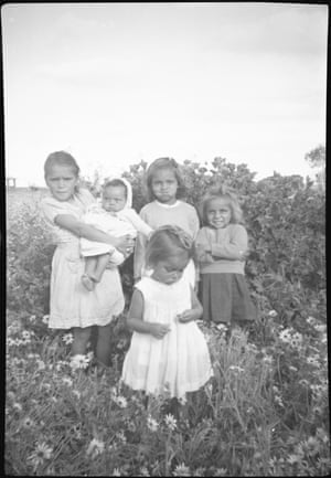 """The """"bush bbies' – Lois, Dallas, Norma, Georgie and Lesley – among the dandelions. Mavis's photos show farm life, football, communions, Sunday-best, gardening, bush tucker trips, family. The subjects are natural and relaxed. A stark contrast to the sombre staged photos often taken by missionaries and authorities."""
