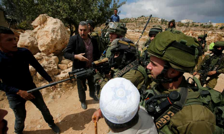 Israeli soldiers and Palestinian protesters in the West Bank city of Hebron  on 6 October.