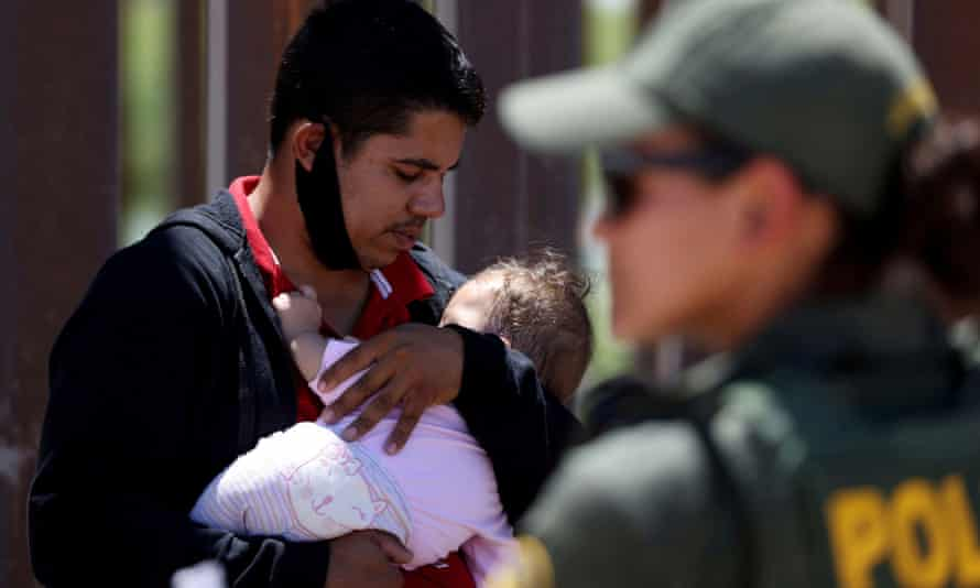 A man seeking asylum holds his infant daughter as they wait to be transported by the US Border Patrol after crossing from Mexico into California on 19 April.