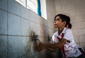 Basel washing his hands in Faihaa school, Basra