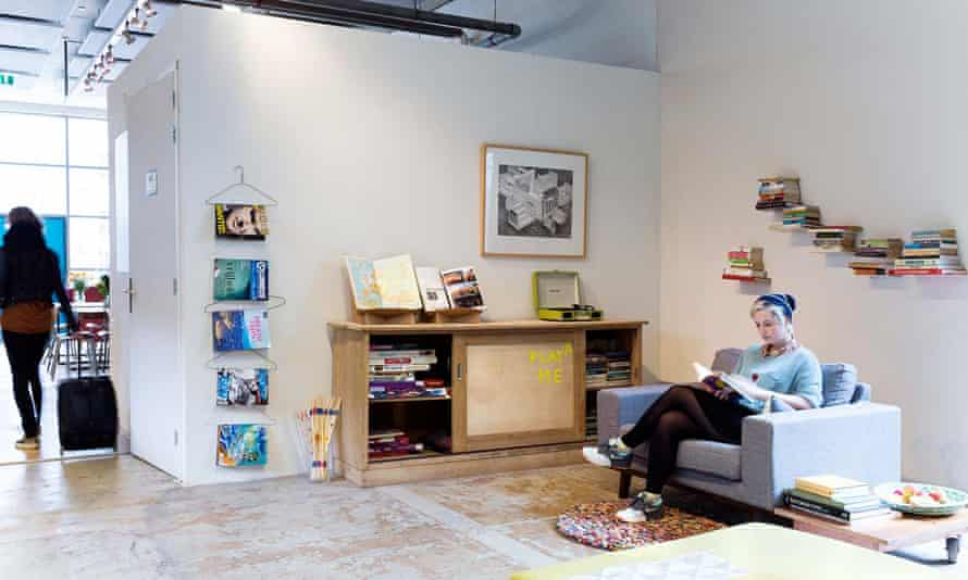A woman sits reading a book in the communal lobby area of Econama Amsterdam