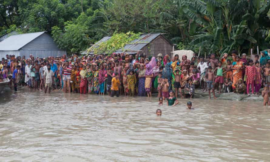 Villagers wait for a boat to escape flooding in Islampur, Jamalpur district, in July 2016