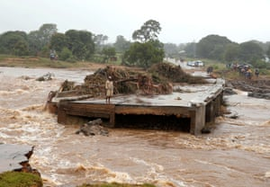 A man looks at a washed away bridge along Umvumvu river, in Chimanimani, on 18 March.