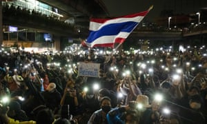 Protesters wave the Thai national flag and shine their phone lights in Bangkok
