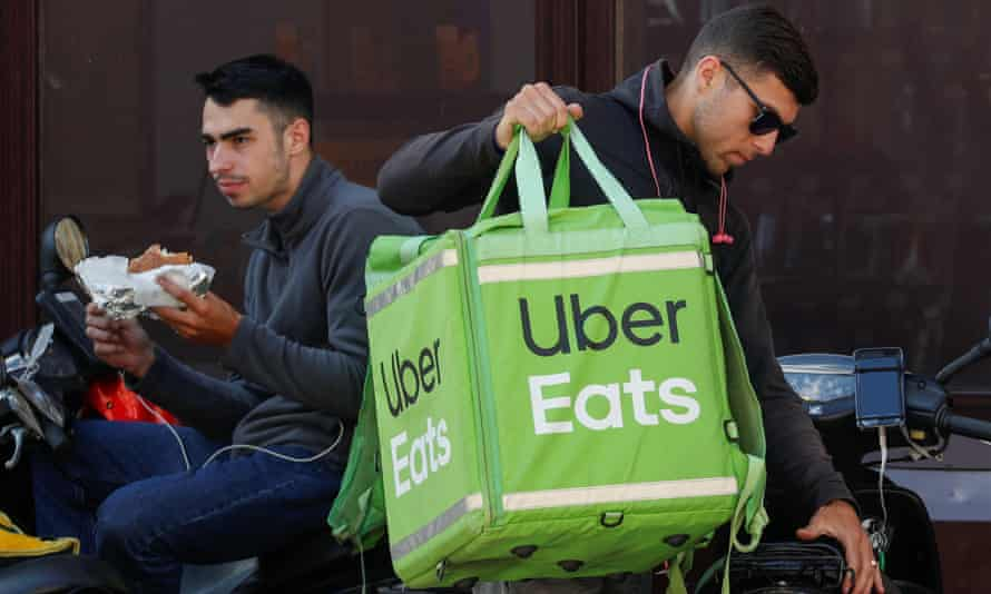 Uber Eats workers wait for orders in central Kiev, Ukraine. Is delivering takeouts the way forward for the company?