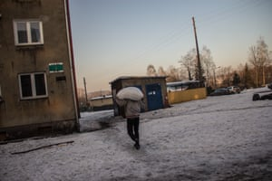 A resident carries a bag of coal scavenged from trains in Bobrek, Bytom