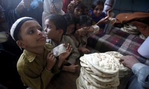 Children queue for subsidised bread at a food distribution centre in Karachi.