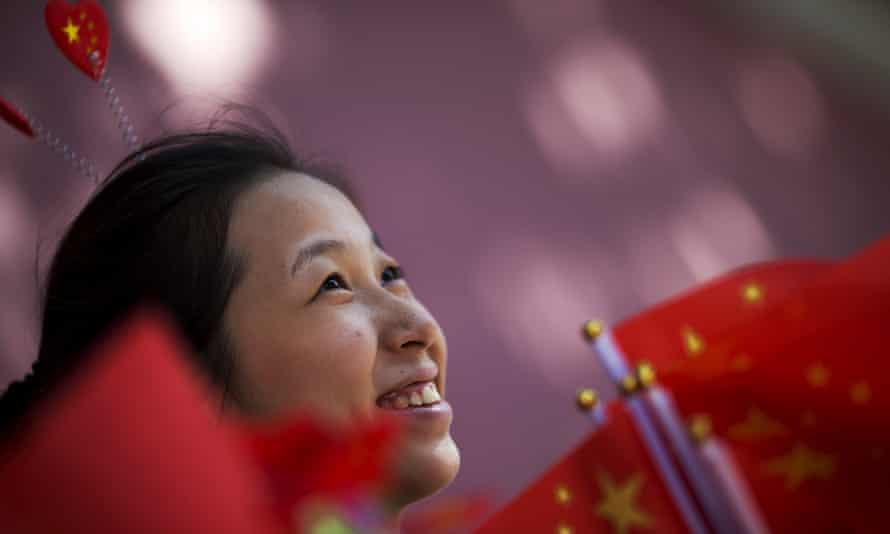 A young woman in Beijing offers flags, stickers and hairpins in national colours to people gathering near Tiananmen Gate to celebrate national day.
