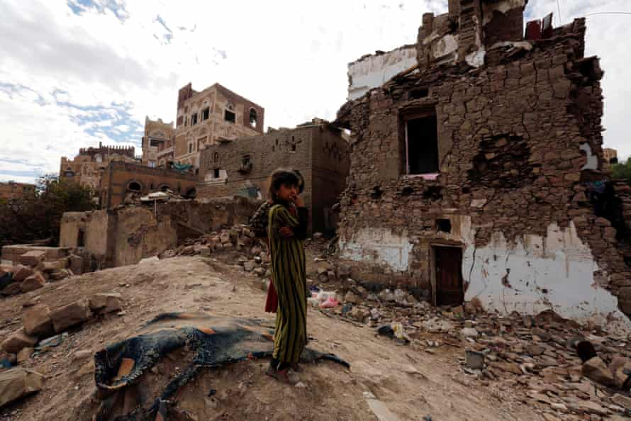 Yemeni girls stand near a building destroyed by an airstrike, in the old city of Sana'a, Yemen