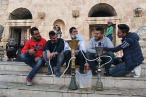 Young men smoke water-pipes in the Old Town of Amman.