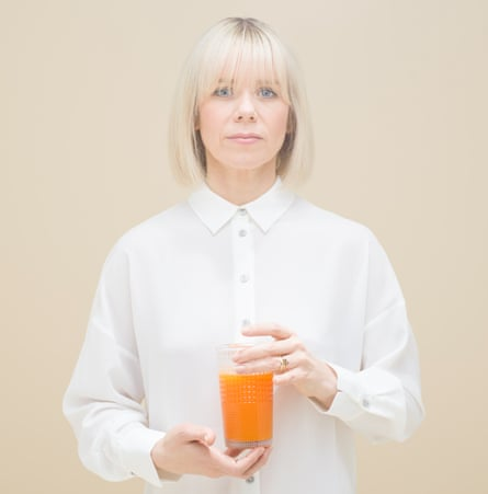 Ruby Warrington holding a glass of carrot juice