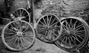 A man repairs a rickshaw wheel.