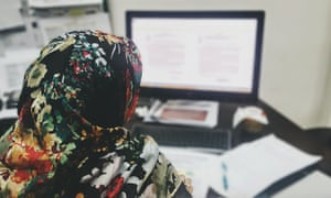 A woman wearing a hijab using a computer