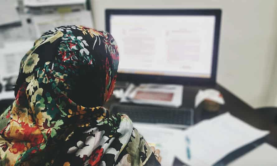 A woman wearing a hijab using a computer