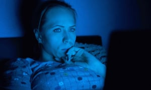 A woman looking at her laptop in the dark