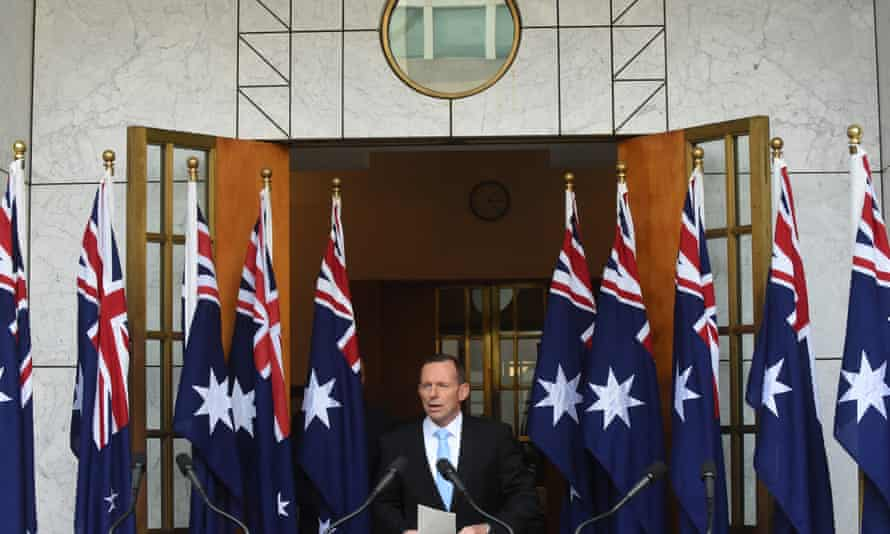 Former Australian prime minister, Tony Abbott, gives a press conference in front of 10 flags