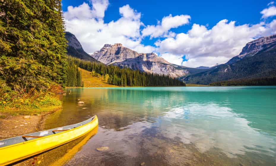 Sunny day in autumn at Yoho national park. In shallow water, the boat is moored.