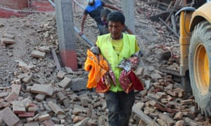 A member of a rescue team takes idols from a fallen temple at Hanuman Dhoka Durbar Square to a safe place