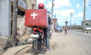 A moped carrying medical supplies is parked up on near the kerb on a road