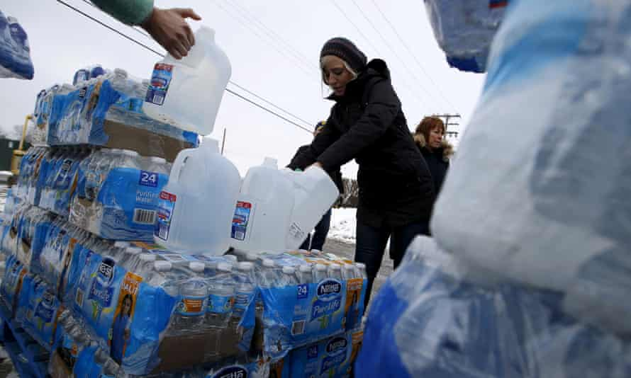 Volunteers distribute bottled water to help combat the effects of the crisis in March.