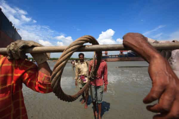 Ship breaking labourers carrying metal rods and rope.