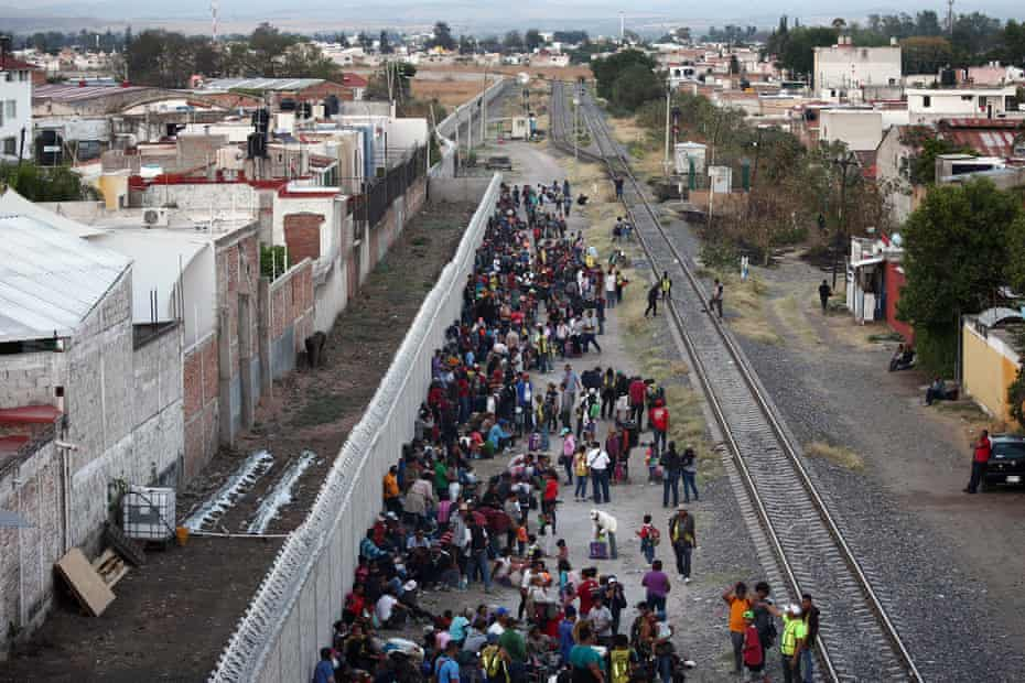 People wait next to the railway to try and board a freight train, in Irapuato, in Guanajuato state, 16 April