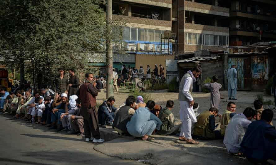 Afghans queue up as they wait for the banks to open and operate at a commercial area of Kabul.