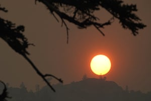 Smoke from the Caldor Fire obscures the sun as it sets over the mountains near the lake.