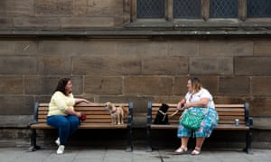 Dog-walkers observe social distancing while meeting up on a street in York.