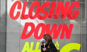 A woman walks past an empty shop in Melbourne