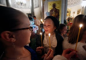 Girls hold candles lit with Holy Fire delivered from Jerusalem