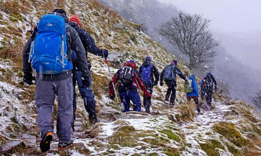 walkers on a steep hillside in snow
