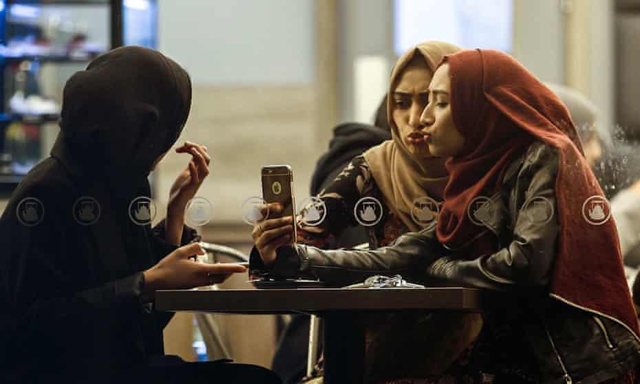 Muslim customers taking selfies at a tea shop in Blackburn in Panorama.