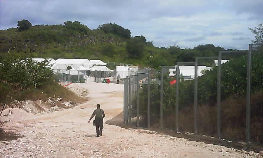 A guard walks towards the entrance of the Nauru detention centre.