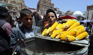 Yemeni children look at corn cobs for sale at a market in Sana'a but prices have soared amid supply issues.