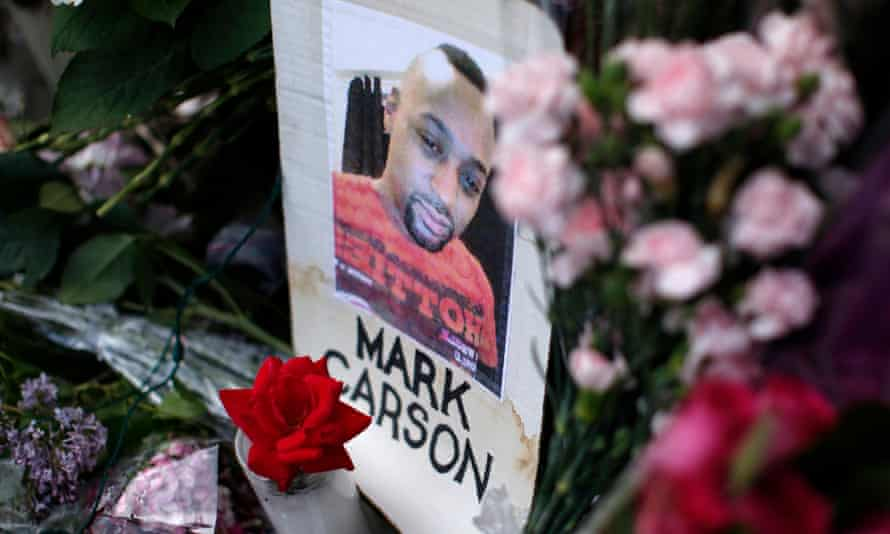 A photograph of the late Mark Carson, a gay man who was shot and killed, sits amid flowers in a makeshift memorial at the site of his murder in New York City.