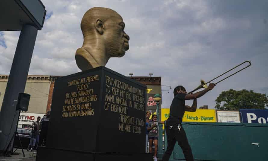 Jonte 'Jonoel' Lancaster plays trombone during a celebration for the refurbished George Floyd statue, after it was vandalized.