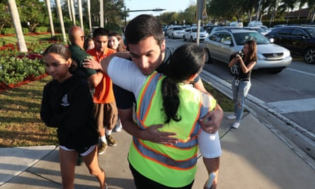 A crossing guard hugs a student as he walks to Marjory Stoneman Douglas high school for the first day of school since the shooting.