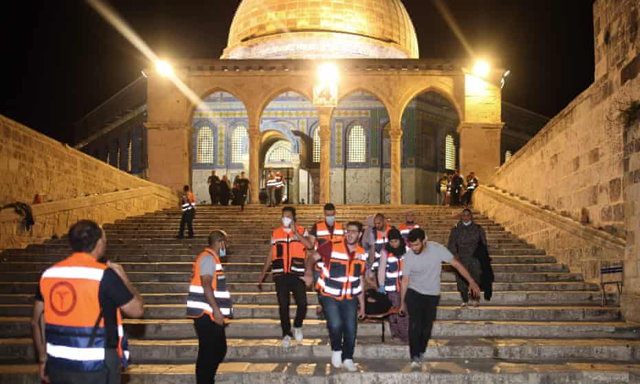 Palestinian medics evacuate a wounded person after clashes in Jerusalem's al-Aqsa mosque compound on 10 May 2021.