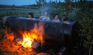 Women bath in a huge tub heated by a bonfire in the remote Siberian village of Bobrovka, Latvia