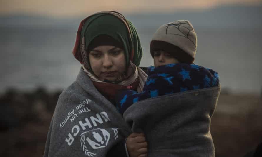 A woman holds a child on a beach near the town of Mytilene, Greece
